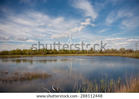 wind turbine located on the green lawn by the lake - stock photo