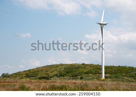 Wind turbine / mill in green environment and a blue light cloudy sky