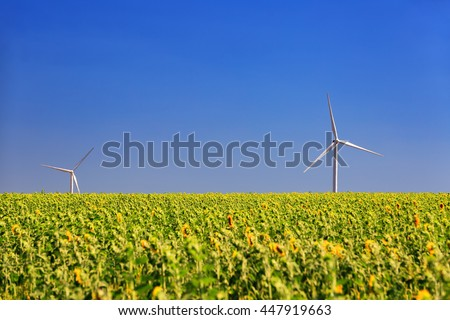 Wind turbine on a background of field and a blue sky on a hot day