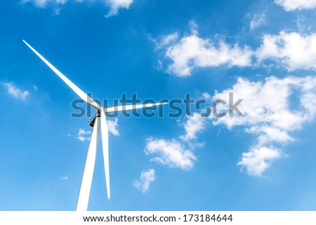 Wind turbine on a bright blue sky background - stock photo