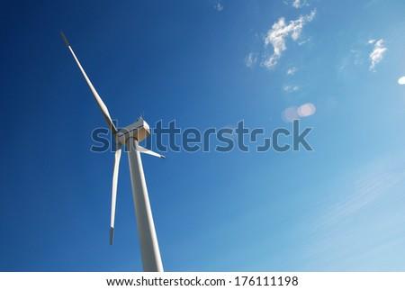 Wind turbine on blue sky - stock photo