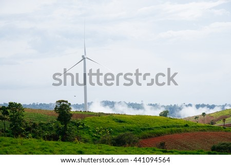 Wind turbine on green field.