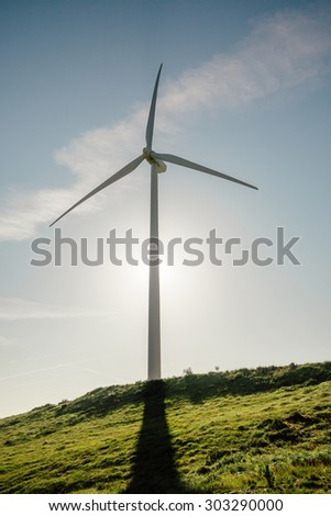 Wind turbine on hill generating electricity over a blue sky background. Clean and ecological energy production concept.