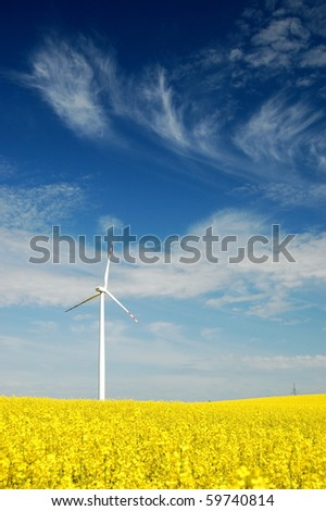 Wind turbine on rapeseed field - stock photo