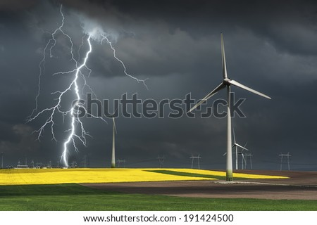 Wind turbine on the green grass over the gray clouded sky - stock photo