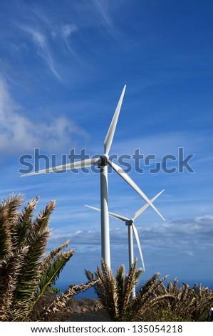 Wind turbine over blue sky on green meadow - stock photo