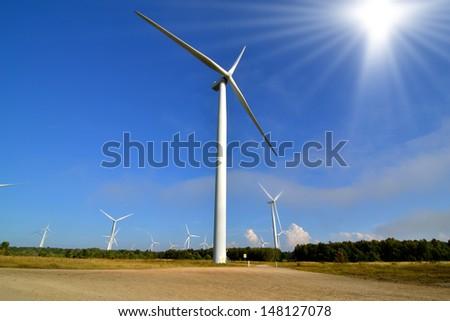 Wind turbine park against the blue sky and shining sun - stock photo