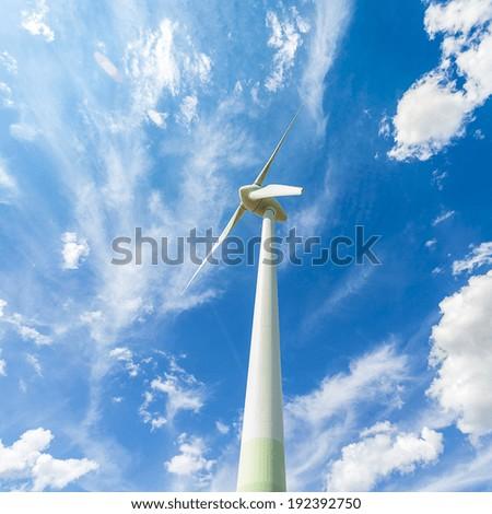 Wind turbine Pinwheel windpower energy industry with blue cloudy sky - stock photo