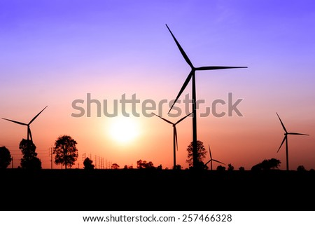 Wind turbine power generator silhouette at sunset - stock photo