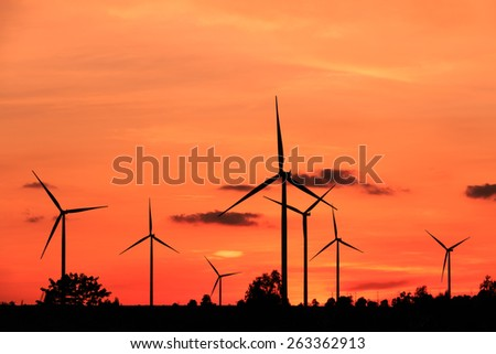 Wind turbine power generator silhouette at sunset