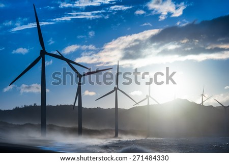 Wind turbine power generators silhouettes at evening ocean coastline. Alternative renewable energy production in Philippines - stock photo