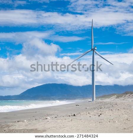 Wind turbine power generators silhouettes at ocean coastline. Alternative renewable energy production in Philippines - stock photo