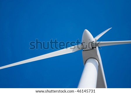 wind turbine propeller blades against blue sky, space for copy - stock photo