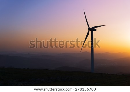 wind turbine silhouette on mountain at the sunset