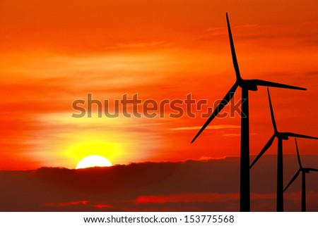 Wind turbine silhouette on sunset background