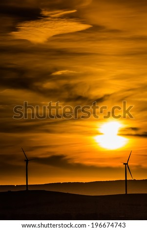 Wind turbine silhouette up on the hill against the background of the sun setting in the dramatic cloudy sky