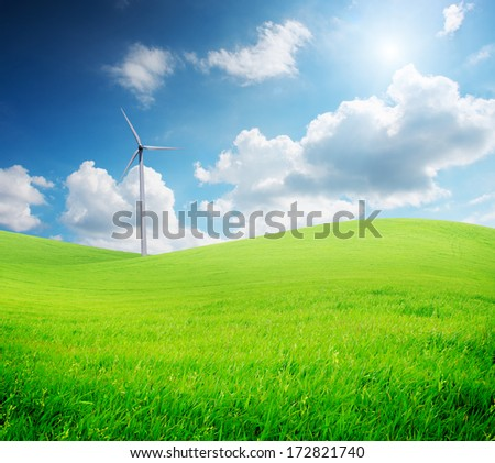 Wind turbine standing on green grass field under blue cloudy sky with sunlight - stock photo
