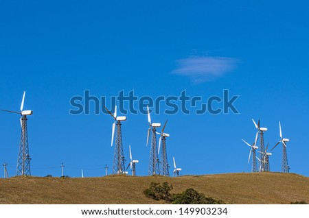 Wind turbine towers over the blue sky