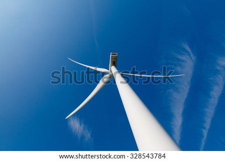 Wind turbine up from the rear and aircraft contrails in the blue sky - stock photo