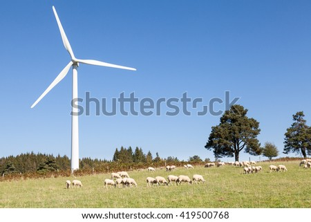 Wind turbine with a flock of grazing sheep on a hilltop against a  blue sky with copy space - sustainable renewable electricity and power  from the kinetic energy of the wind alongside  agriculture - stock photo