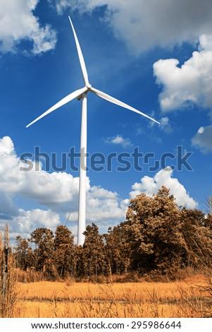 Wind turbine with blue sky, summer field, renewable energy - stock photo