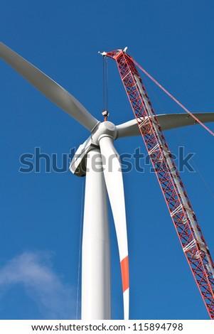 Wind turbine with crane in construction - stock photo