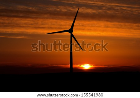 Wind turbine with nuclear powered sun at sunset near Gooseham in Cornwall England