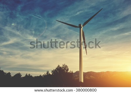 Wind turbine with rays of light at sunset, electric generator with amazing evening cloudy sky on background, renewable and alternative energy sources, windmill in countryside  - stock photo