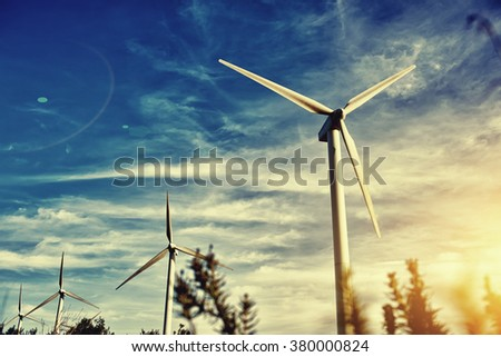 Wind turbines against beautiful cloudy sky, electric generators in countryside with sun says on background, renewable energy sources, windmills outside the city