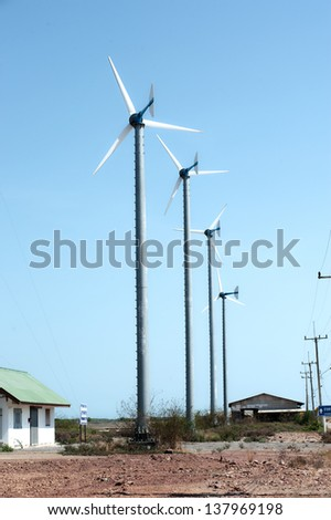 Wind turbines against blue sky produce electricity.