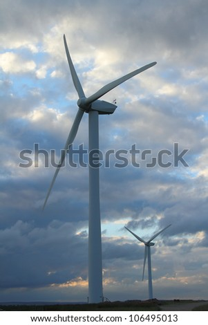 wind turbines against cloudy sky
