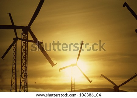 Wind turbines against golden sky - stock photo