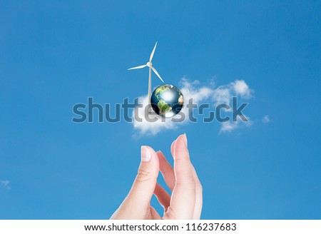 Wind turbines and earth with hand over blue sky (Elements of this image furnished by NASA)