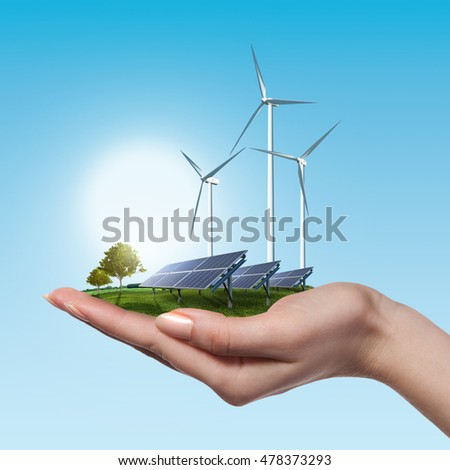 Wind turbines and solar panels in female hand