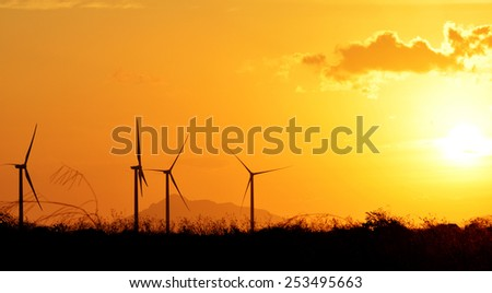 Wind turbines as silhouettes against a beautiful sunset