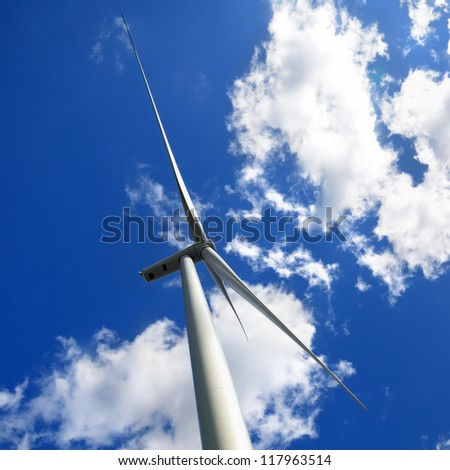 wind turbines at the meadow against blue sky - stock photo