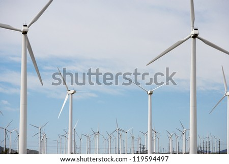 Wind turbines at wind farm against cloudy sky