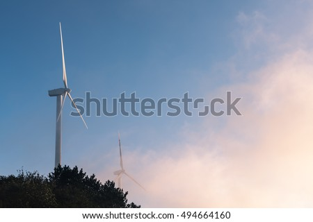 wind turbines closeup in early morning ,clouds and mist involve the mountain top
