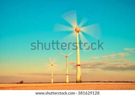 Wind turbines farm at sunset in morning meadow. Vintage Style Toned effect - stock photo