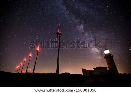 wind turbines generating clean power with lighthouse on the milk way - stock photo