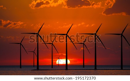 Wind turbines generating electricity at sunset - stock photo
