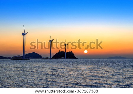 Wind turbines generating electricity at sunset in Korea. - stock photo