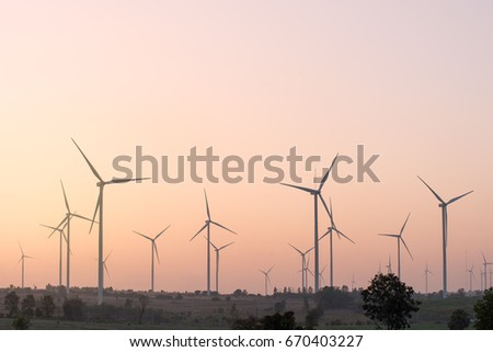 Wind turbines generating electricity at sunset, renewable energy