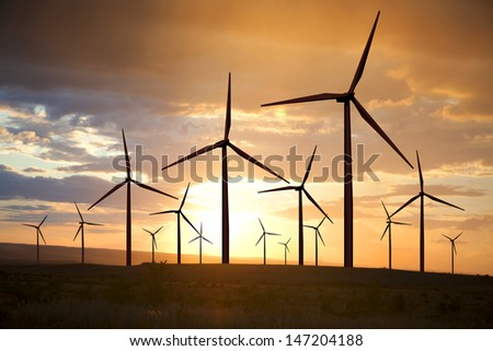 wind turbines generating electricity on sunset sky