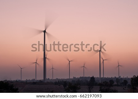 Wind turbines generating electricity spinning at sunset