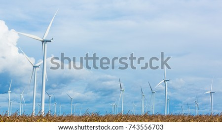 Wind turbines generating electricity with blue sky energy conservation concept