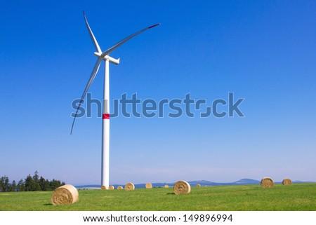 Wind turbines in a green field - stock photo