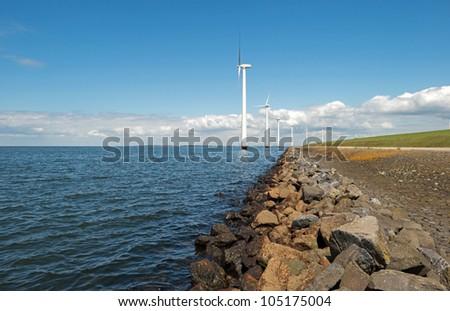 Wind turbines in a lake along a dam - stock photo