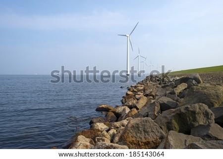 Wind turbines in a lake along a dike - stock photo