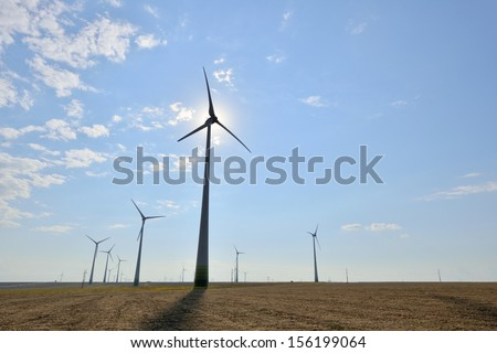 Wind turbines in contre-jour in a sunny summer day